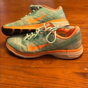 Teal and orange Nike running shoes. Small scratch.